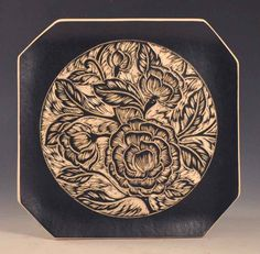 Victoria Plate by Sara Meehan. Intricate wild rose design graces the center of this hand carved porcelain plate. dramatic soft black border with cream glazing.