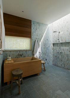 In the master bath, Hale chose slate tile for the floors and green-and-brown glass tile by Lunada Bay for the walls, both from United Tile. The Japanese Ofuro soaking tub, crafted from Hinoki wood, is by Zen Bathworks. #tiburon #california #kithome #bathroom #soakingtub