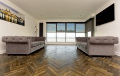 The dark rustic tones of Zigzag Foundry Steel herringbone wood floors featuring inside a modern Liverpool Docks apartment design