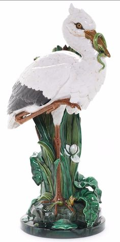 Minton Majolica Stork, circa 1870, by John Henk, modeled standing on one leg, frog beneath one foot and a snake in beak, on circular base, 77cm high, impressed 'Mintons'