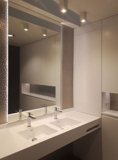 Baño minimalista. Revestimiento en porcelánico imitación mosaico de metal. Lavabos termofundidos en encimera de solid surface. Mobiliario realizado en DM lacado blanco satinado. Espero con iluminación trasera indirecta de led. Diseño de interiores realizado y coordinado por AZ diseño.