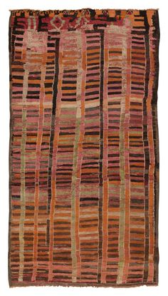 Vintage Moroccan Rug, Morocco, Mid 20th Century - Created in Morocco, this colorful vintage rug features a vibrant stripe pattern rendered in a high-contrast combination of tourmaline pink, watermelon green, burnt orange, ivory and walnut brown. Vibrant stripes traverse the field morphing into a series of irregular glyphs set over a rich cerise background.