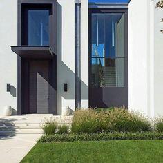 By Blaze Makoid Architecture. Fachada branca e cinza, jardim frontal.