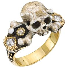 Memento Mori Skull Ring. Memento Mori skull ring, intricately carved in gold and multicolored enamel, with a smaller and larger rose-cut diamond accent at either shoulder, mounted in 18k yellow gold. 20th century.