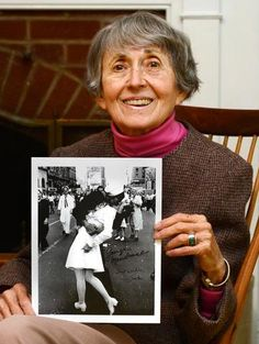 AW!! this is the lady that is in my most favorite photo EVER!!   Greta Friedman, of Frederick, holds an autographed copy of the famous Life magazine photo by Alfred Eisenstaedt taken in New York's Times Square on V-J Day in 1945. Authors of a new book say they have proved the people in the photo are Friedman and George Mendonsa. (Courtesy Sam Yu/Frederick News Post)