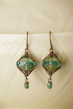 These handmade Czech glass gemstone dangle earrings inspire a vintage look with antique brass wire and blue/green glass. Finished with antique brass (lead and nickel-free) earwires. Czech glass, ant