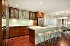 This glass backsplash in Vancouver is more understated, allowing the ruddy glow of the cabinets to take center stage. The monochromatic backsplash also makes the kitchen look bigger.