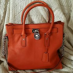 MICHAEL KORS LARGE HAMILTON SATCHEL This Gorgeous orange satchel is perfect for fall!  The orange w/silver are hard to find in excellent condition.  Silver mirror-metalic trim and lock.  Made of Genuine Saffiano Leather  Leather short handles and a long chain and leather handle.  Fully lined & 5 pockets inside  Magnetic snap  It is very roomy and was gently used only once.  It's in perfect condition with NO flaws!  Like Brand New!  NO Trades please! Michael Kors Bags Satchels