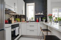 czarno-biała kuchnia,mała kuchnia,nowoczesna kuchnia,skandynawska kuchnia,czarne płytki na scianę,białe szafki kuchenne,nowoczesne hokery