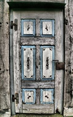 Love this grey, blue and white weathered wooden door -- complete with hand-painted flourishes
