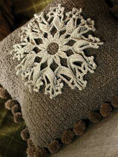 Knit this stylish cushion with crochet motif and pom pom detail from our British