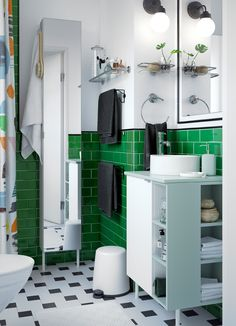 Hvidt, grønt og sort badeværelse med hvidt skab med vask med åben og lukket opbevaring.