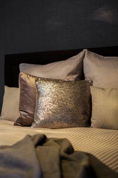 Damit der monochrome Raum in Grau nicht zu hart wirkt. Unterstreichen glänzende Kissen den glamourösen Touch: Auf heller Bettwäsche wirken Hüllen mit Pailletten oder aus feinstem Samt wie luxuriöse Hingucker. Die schimmernden Oberflächen zaubern sofort eine sinnliche Atmosphäre.