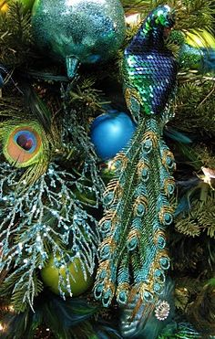 Not just peacocks, but I love stuffing the tree with non-traditional items! It helps with spaces/holes and if you have a pre-strung tree (lights) and a string goes bad, it will camouflage the dark spots ; Peacock Christmas Decorations, Peacock Christmas Tree, Peacock Ornaments, Peacock Decor, Peacock Theme, Christmas Tree Themes, Blue Christmas, Christmas 2015, Christmas Colors