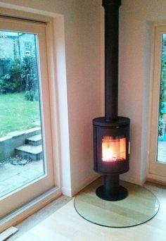 Circular glass hearth for circular or cylindrical stove Corner Log Burner, Wood Burning Stove Corner, Wood Burning Logs, Corner Stove, Wood Burner Fireplace, Fireplace Hearth, Fireplaces, Freestanding Fireplace, Small Fireplace