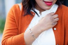 Investing in a classic wardrobe is the key to saving money over time. Keep reading for tips on the how and why and start saving.   Orange cardigan, ruffle blouse, with booties.