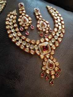 Kundan & Ruby Set- Kundan has always been the most preferred and favorite work for the brides out there. Team it up with ruby stones to add a jazz to your bridal jewellery. It's intricately made, is elegant and delicate to wear. The golden plating is adding a finishing touch to this jewellery set. It would look with both lehenga and sarees.