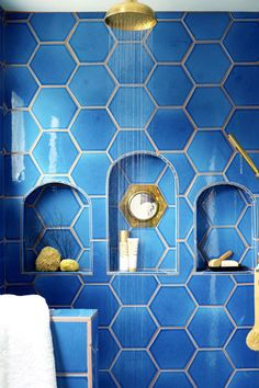 "Shampoo storage never looked so chic. In Justina Blakeney's ""Jungalow,"" the shower's niche is inset with a vintage mirror. Adriatic Sea hexagonal tiles are by Fireclay Tile. Click through for more of the best bathroom design ideas."