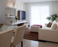 Home theater com prateleiras brancas, sendo o painel na cor cinza (em laca) com 30cm de sobra da tv para cada lado e o móvel do chão em madeira