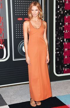 Karlie Kloss in an orange dress with beading and lace-up gold sandals