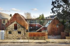 After: Now the house is a stunning property consisting of two wings. Each wing of the house has also been clad with pre-fabricated weathered steel. The two parts are connected by two glass walls, which allow plenty of sunlight in and break up the wooden theme