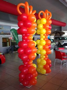 red orange and yellow tall balloon columns-great for car, furniture or large product sales events Balloon Pillars, Balloon Tower, Balloon Cars, Balloon Stands, Balloon Backdrop, Balloon Decorations, The Balloon, Balloon Ideas, Dance Themes