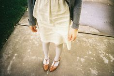 cream dress, white tights and tan strappy shoes. winsome.