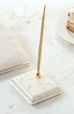 """Lillian Rose Ivory Embroidery Pen Set This pen set includes a gold pen with black ink and a 3.25"""" x 3.25"""" ivory satin pen base. The base is embroidered with a leaf and vine pattern. A matching guest book is sold separately. Also available in white. Price $15.90"""