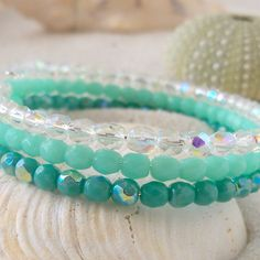 This listing is for an oval, glass beaded memory wire bracelet, with Teal and clear glass beads. The beads are 4mm Czech glass beads. This