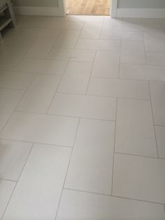 """This master bathroom shows a 12"""" x 24"""" neutral tile, with light gray grout, installed in a herringbone pattern."""