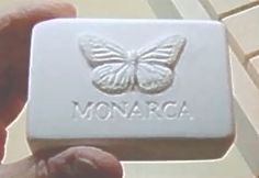 """Monarca Soap Bar Plaster Prototype. 3.5"""" long x 2.375"""" wide x 1.1875"""" thick. Slightly rounded edges, Monarca Lettering engraved, raised butterfly artwork. Company Located in Connecticut, United States."""