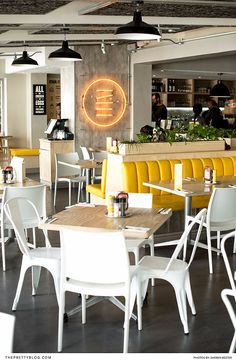 With its vibrant yellow booths and grey, concrete-like floors, Stacked Diner sports a contemporary and minimalistic aesthetic. Espresso Cafe, Burger Toppings, Real Quick, Dining Chairs, Minimalist, Flooring, Fresh, Contemporary, Concrete
