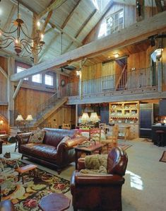 The third level of this timber frame barn contains a large loft room with a window that overlooks the great room. Wood walls and ceilings maintain an authentic barn feel.
