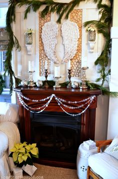 Christmas Mantel...Birch Tree Candle...tutorial here, angel wings & mercury glass from Marshalls, garland made from wax paper,  and I love the corbels holding candles!  Beautiful mantel!