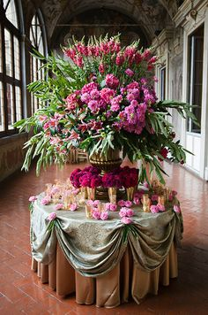 A fantastic floral arrangement of pink blooms and various greens compliments small gold vases at the base.