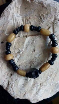 Armband gemaakt van zwarte houten kralen, kralen gemaakt van bot en een zwart doodskop.