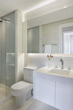 Banheiro: Branco com pastilhas claras no box, espelho do tamanho da parede e pia embutida na cuba