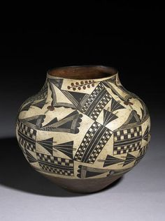 An Acoma polychrome jar With an allover pattern of geometric checkered panels and triangular motifs, stylized floral accents.height 10 3/4in, diameter 12in