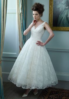 All-over lace dress, in a 50s style. With a finely draped crossover V-neckline and back, a draped bodice, and full circle ankle-length skirt. Also available long with a mid-length train. Fabric Silk dupion & French lace