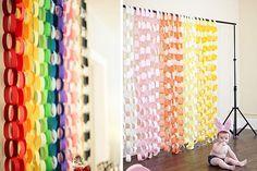 Para realizar este fondo sólo necesitamos tijeras, pegamento o celo y cartulinas de colores o papel crepe. Cortamos en tiras del mismo tamaño – podemos utilizar una regla para ser más precisos- y unimos las puntas entrelazando unas cintas con otras a modo de cadena. ¡Así de fácil! #Photocall #DIY
