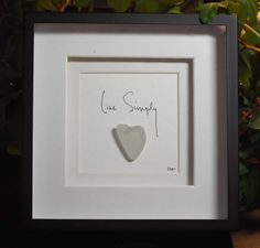 Live Simply is an original design of a genuine sea glass heart with hand lettering in a 6 square black shadowbox frame. What a beautifully simple design that would nicely compliment any home or office decor. This piece is the perfect gift for anyone and any occasion. As with all of my artwork, each piece is an original and once that piece is sold, I can create a custom duplicate - made to order and includes the matting and frame, making it a complete piece; perfect for gift giving. Each…
