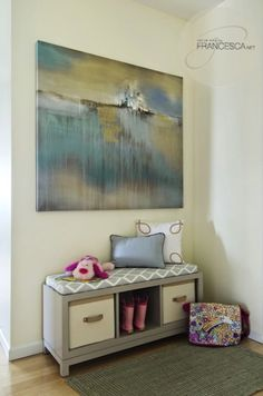 Beautiful foyer with pale yellow walls paint color, blue & yellow landscape canvas painting, gray storage bench, white & gray lattice cushion and gray rug.