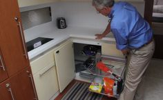 Beneteau Gran Turismo 49: The roomy galley has a lot of innovations, including this wire storage shelf that reveals a second one when the first is pulled out. A two-burner ceramic stove is just to the left. Decking can be either Piemont or Milano oak laminated floors. The cabinets are offered in White-lacquered (standard) or cream-lacquered units.