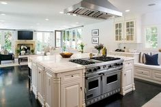 Amazing kitchen features a stainless steel vent hood placed directly above an extra large square ...