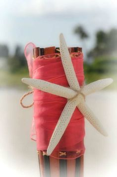 The coral sash brings a pop of color and the starfish adds the perfect style for a perfect Florida beach wedding by Suncoast Weddings