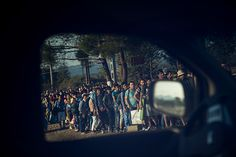 Migrants, seen through the window of a police car, wait at the Greek-Macedonian border for Macedonian police to allow them to cross. September 2015 (Santi Palacios/AP) ProPublica
