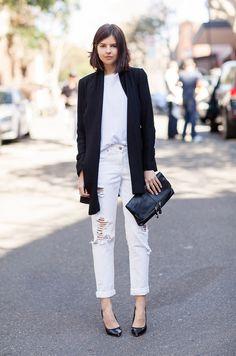 Street style look com calça jeans branca, perfeita para dias de trabalho durante o Outono e Inverno, com um blazer preto e salto alto