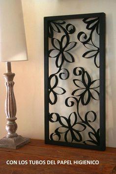 Simulando una reja, marco de madera y flores hechas con tubos de carton del papel higienico o rollos de cocina, cortados y armado como flores pintadas de negro.