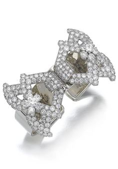 Pair of diamond clips/bracelet, Cartier, circa 1940. Each of stylised swag design, set with single- and circular-cut diamonds, mounted in platinum, to be worn together on a bangle fitting, mounted in yellow gold, all signed Cartier Paris and numbered, French assay and maker's marks. #Cartier #retro #bangle #clips