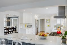 timeless white kitchen design - Navy counter stools and gray kitchen island